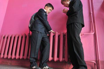Школьники у батареи парового отопления согревают руки дыханием.